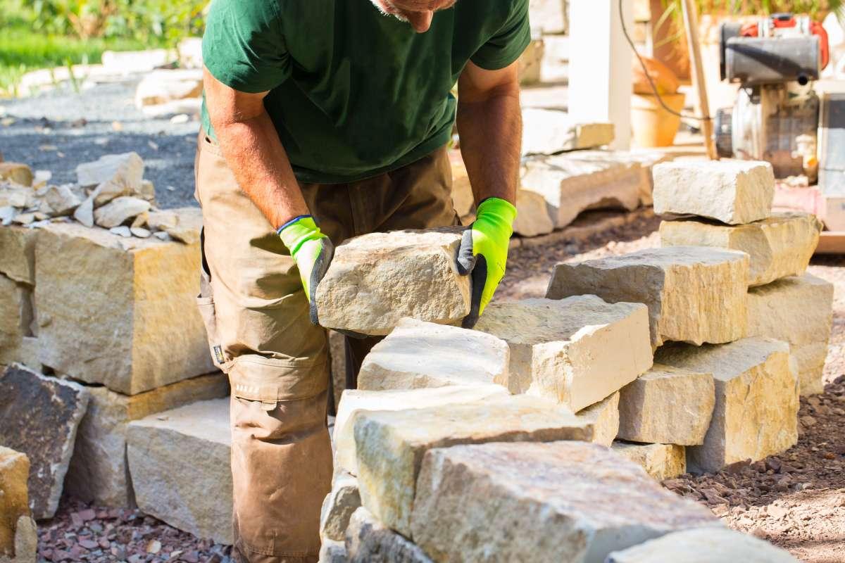 Mann baut Trockenmauer aus Sandstein